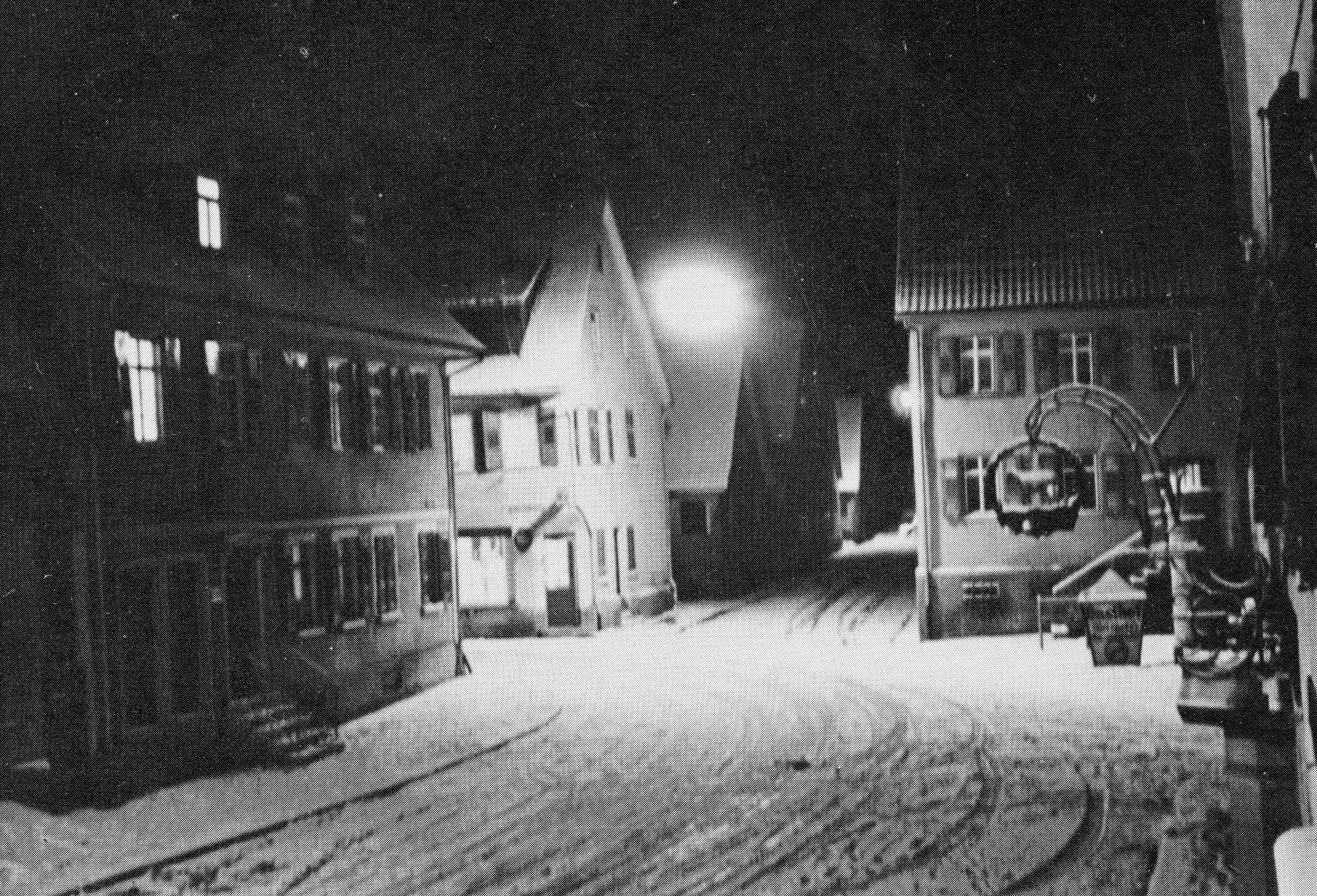 """Das 1974 abgebrochene Haus ganz links, ehemals Hauptstraße 15, war bis Ende 1938 das Wohnhaus der Familie Weil. Rechts ist das Wirtshausschild des """"Lamm"""" zu sehen, dahinter das Haus der Familie Jordan."""